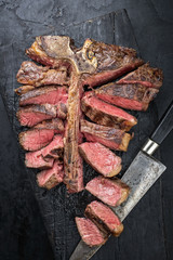 Barbecue dry aged wagyu porterhouse steak sliced as top view on a burnt board