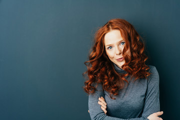 Young red-haired woman against dark background