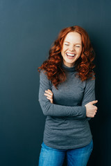 Young laughing red-haired woman on dark background