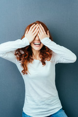 Vivacious laughing young woman covering her eyes