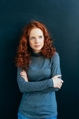Thoughtful young redhead woman thinking deeply