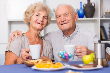 Happy senior couple enjoying conversation over cup of coffee