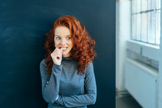 Worried young woman biting her nail in trepidation