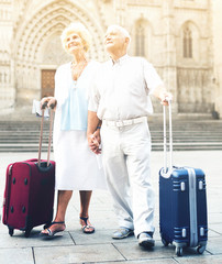 Senior woman and man travelling together, walking with baggage on city