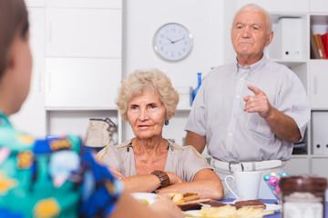 Upset elderly pair having tough talk with girl