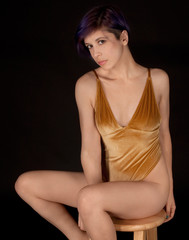 Woman in Gold Velvet Bodysuit Seated on Stool