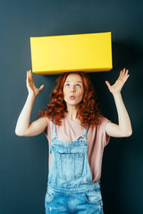 Young red-haired woman with yellow box on her head