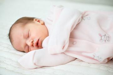 Portrait of newborn baby girl sleeping at home