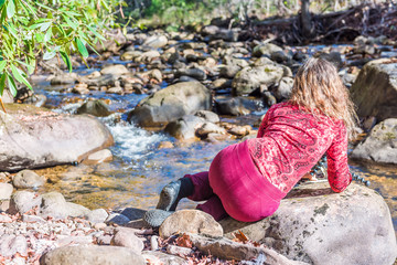 Woman back in red lying down taking pictures of shallow rock stream with running water and waterfall in autumn with green leaf foliage, stones and flowing creek