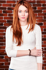 Beautiful Redhaired Young Woman posing over Red Brick Wall. Casual Natural Looking Girl.