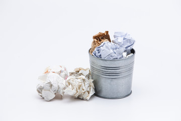 Crumpled business papers with metal pot concept view on white