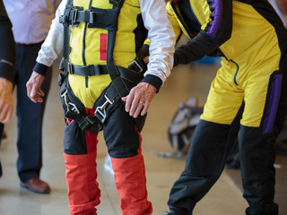 Skydiver Instructor Helps Apprentice to Tie Security Belt on His Parachutist Suit