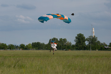 Parachutist with Blue Parachute against Clear Blue Sky