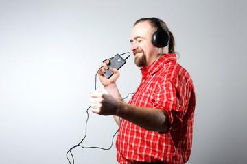 Bearded man in headphones listening to music.