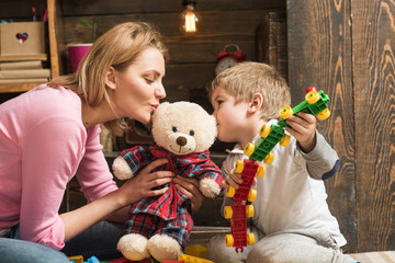 Kindness and education concept. Mother teaches son to be kind and friendly. Nursery wooden wall on background. Family play with teddy bear at home. Mom and child play with soft toy.