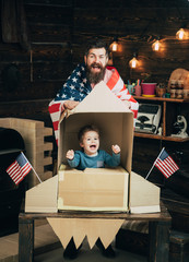 American cheerful family with usa flags play with rocket made out of cardboard box. Rocket launch concept. Kid happy sit in hand made rocket with usa flags. Child cute boy play cosmonaut, astronaut.
