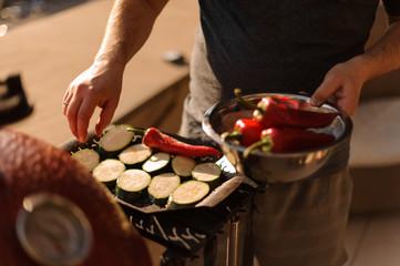 Man hands preparing fresh vegetables for grill