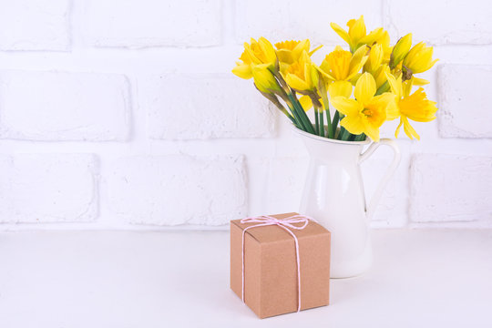 Jar with narcissuses and a gift box at the white background. Spring, mothers day and easter concept