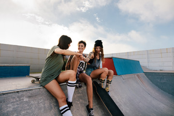 Three women hanging out at skate park.