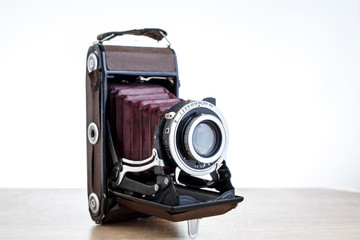 Old vintage camera on table, white background