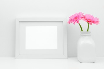 Mock up white frame and pink daisy flowers in vase on a shelf or desk. White color scheme. Landscape frame orientation.