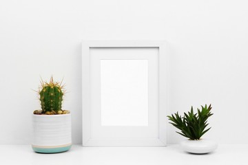Mock up white frame with cactus and succulent on a shelf or desk. White color scheme. Portrait frame orientation.
