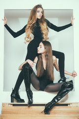 Fashionable ladies with make up and skinny legs posing, white background. Girls with long hair on mysterious faces posing in black clothes. Fashion and beauty concept. Ladies slim wear tight clothes.