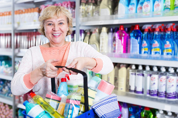 Female in store holding basket with chemical products