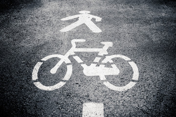 Pedestrian and cycle lane sign or symbol painted on asphalt. Black and white. Vertical shot.