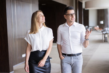 Smiling male executive showing office to female colleague. Young Caucasian businessman wearing glasses walking with female partner and talking in office building. Meeting, employment concept