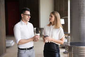 Smiling young colleagues talking at coffee break. Young Caucasian businessman wearing glasses and businesswoman holding takeaway coffee communicating. Business break concept
