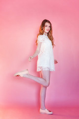 Happy teenage girl smiling. Closeup portrait young happy positive woman wearing white dress standing on pink colourful pastel trendy modern fashion pin-up background. European woman. Positive human em