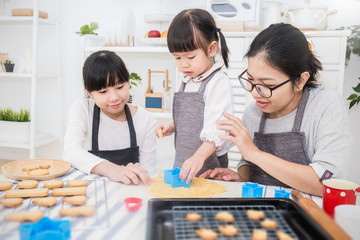Portrait of little asian girl with her sister and mother baking cake and cookies in the kitchen. Happy asian family education and mother's day concept