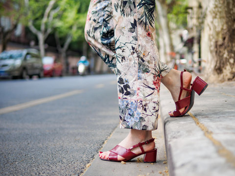Close up on girl's feet wearing red sandals in the city, urban road background.