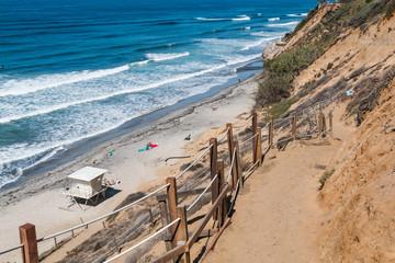 A dirt trail leading toward the beach and a lifeguard station at Beacon's Beach in Encinitas, California.