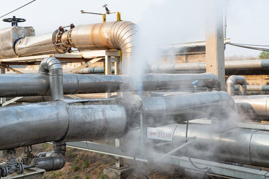 Leakage of steam in heat pipeline interior industrial gas with a lot of piping. Steam valve piping in factory
