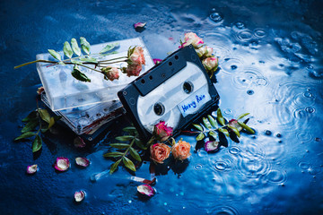Audio cassette tape with Heavy Rain label in a scene with rose petals and raindrops. Melancholy music for rainy weather. Nostalgia concept copy space.