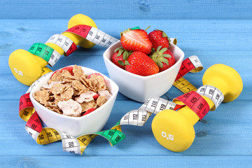 Fresh strawberries, wheat and rye flakes, dumbbells and centimeter, concept of healthy and sporty lifestyle