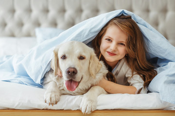 Beautiful little girl with golden retriever dog in a bed