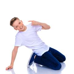 A cheerful little boy from school age is dancing breakdance.