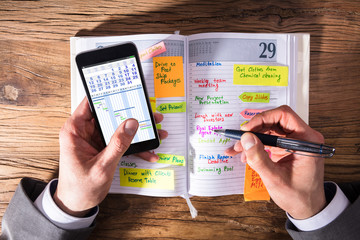 Fototapete - Businessperson With Mobile Phone Writing Schedule In Diary