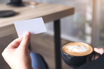 Woman holding an empty business card while drinking coffee cup