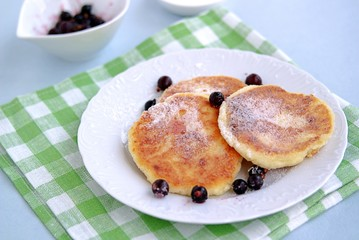 Breakfast. Curd cheese cakes with sour cream and currants sprinkled with powdered sugar.