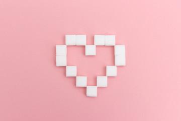 Herz aus Würfelzucker auf rosa Hintergrund
