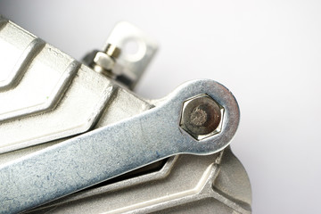 the key for twisting the nuts of the hexagonal form unscrews the bolt from the metal unit
