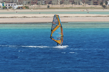 the windsurfer on the board under sail moves at a speed along the surface of the sea,