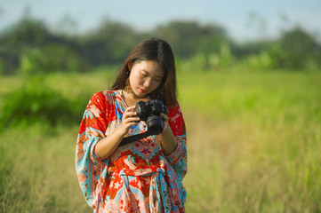 sweet young Asian Chinese or Korean woman on her 20s checking picture in photo camera in beautiful nature landscape in holidays