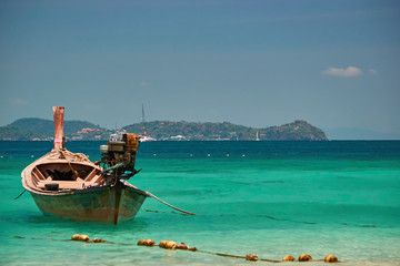 Concept tropical paradise. Wooden fishing boat in the turquoise waters on the background of the Islands and blue sky in sunny day.