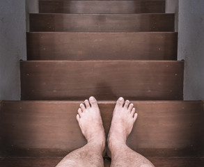 The barefoot man was walking down the stairs.