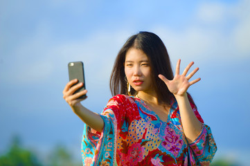 young beautiful and happy Asian Chinese tourist woman on her 20s with colorful dress taking selfie pic with mobile phone camera on tropical field